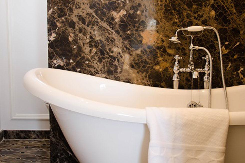 Salle de bain en marbre et baignoire sur pied d'une chambre Supérieure - Villa Victor Louis